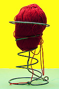 spiral with red knitting wool object on yellow green background