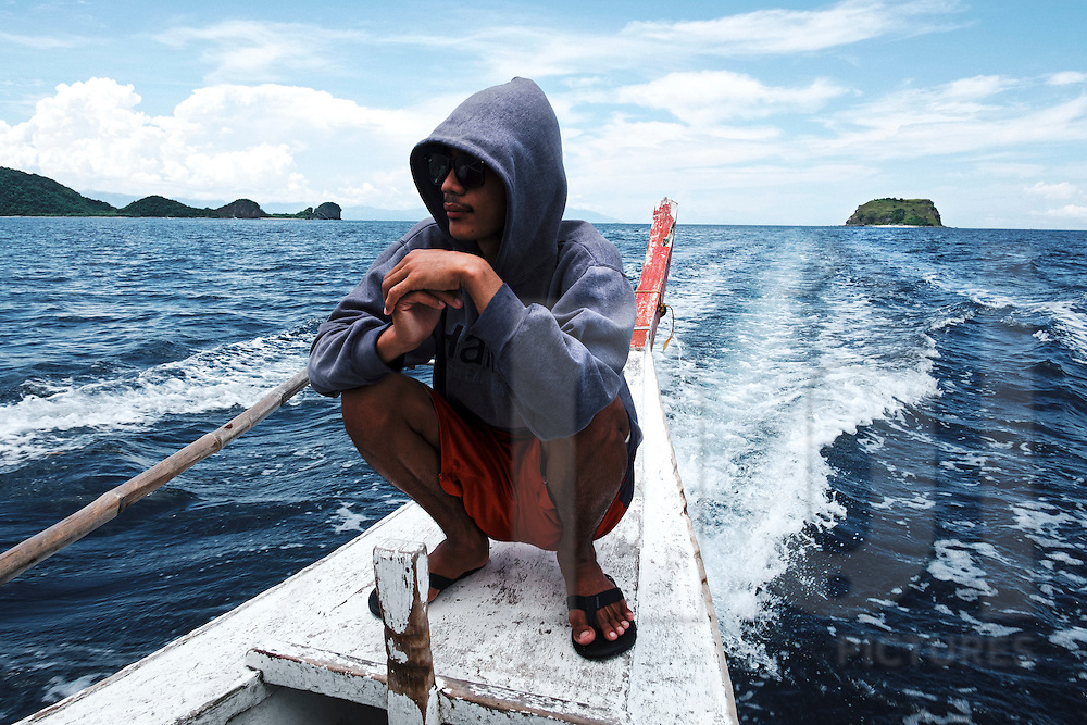 A filippino squats at the back of a bangka boat offshore of  Luzon Island, Philippines, Southeast Asia, 2016