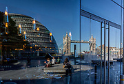 A riverside cafe reflection of City Hall and Tower Bridge, on 26th September 2018, in London, England.