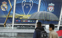 May 13, 2018 - Kiev, Ukraine - Couple under the umbrella walks past NSC Olimpiyskiy Stadium covered with banners for the Champions League in Kyiv, Ukraine, May 13, 2018. Kyiv prepares to host UEFA Women's Champions League final between Wolfsburg and Lyon at Valeriy Lobanovskiy Dynamo Stadium on 24 May, 2018 and the UEFA Champions League final match between Real Madrid and  Liverpool at NSC Olimpiyskiy Stadium on Saturday 26 May, 2018. (Credit Image: © Sergii Kharchenko/NurPhoto via ZUMA Press)