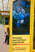Rwanda February 2014. Kigali . A young man looks at his phone whilst sitting waiting in a bus shelter which has adverts for a mobile phone company -MTN - and encourages customers to send and receive money via a phone.