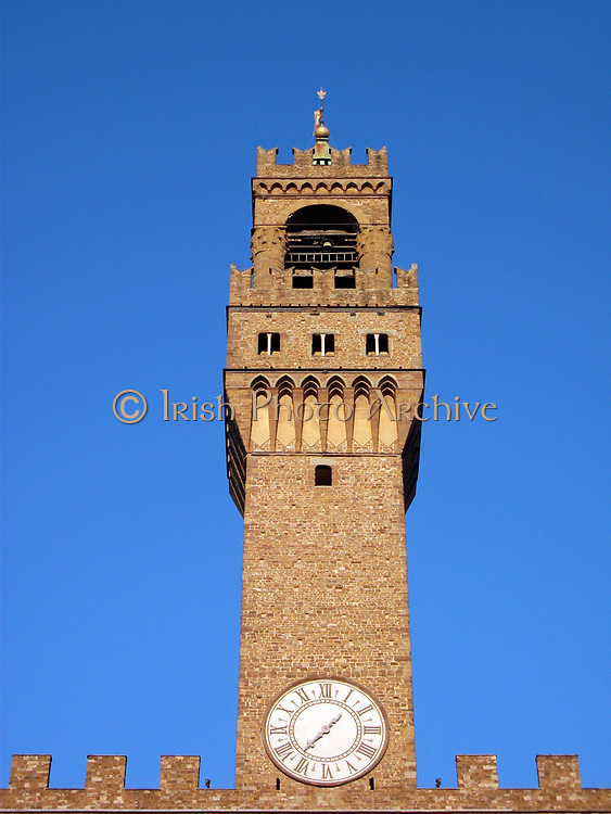The clock tower of the Palazzo Vecchio. Town hall of Florence, Italy. A huge Romanesque fortress-palace overlooking the Piazza della Signoria. Designed by the architect Arnolfo di Cambio in 1299. A stonework cubicle building forms the base, crowned with a projected battlement clock tower. The current clock was made by Vincenzo Viviani in 1667. Arches in the structure are decorated with the 9 coats of arms of the Florentine Republic.