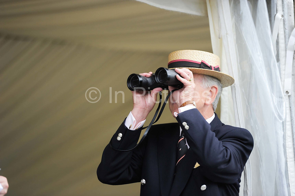 Spectator in a straw boater hat and blazer watches rowing races through his binoculars at the Henley Royal Regatta, an annual event first held in 1839 in Henley-on-Thames, southern England. Off the water, competitors and spectators must adhere to the strict rules that have traditionally governed the dress and comportment of the British upper classes at play.