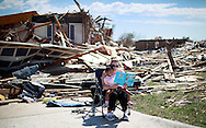 Sarah Dick reads a Doctor Suess book to her three-year-old daughter Jadyn in the driveway of her tornado destroyed house in Oklahoma City, Oklahoma May 22, 2013. Rescue workers with sniffer dogs picked through the ruins on Wednesday to ensure no survivors remained buried after a deadly tornado left thousands homeless and trying to salvage what was left of their belongings.  REUTERS/Rick Wilking (UNITED STATES)