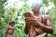 Surui indians using GPS geolocalisation inside Surui territory primary rainforest interior.<br /> <br /> An Amazonian tribal chief Almir Narayamogo, leader of 1350 Surui Indians in Rondônia, near Cacaol, Brazil, with a $100,000 bounty on his head, is fighting for the survival of his people and their forest, and using the world's modern hi-tech tools; computers, smartphones, Google Earth and digital forestry surveillance. So far their fight has been very effective, leading to a most promising and novel result. In 2013, Almir Narayamogo, led his people to be the first and unique indigenous tribe in the world to manage their own REDD+ carbon project and sell carbon credits to the industrial world. By marketing the CO2 capacity of 250 000 hectares of their virgin forest, the forty year old Surui, has ensured the preservation, as well as a future of his community. <br /> <br /> In 2009, the four clans and 25 Surui villages voted in favour of a total moratorium on logging and the carbon credits project. <br /> <br /> They still face deforestation problems, such as illegal logging, and gold mining which causes pollution of their river systems