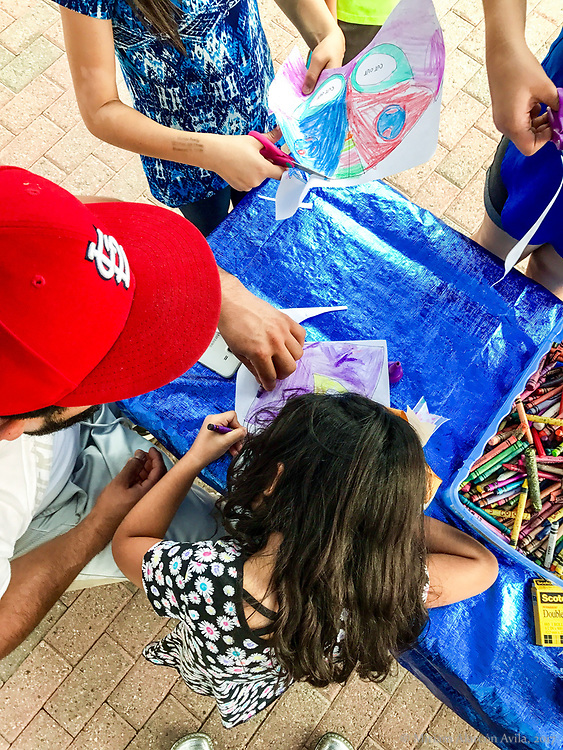Latino and Latina kids making paper luchador masks during Latino festival in West Liberty in Iowa in September of 2017.