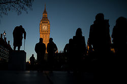 © Licensed to London News Pictures . 25/03/2017 . London , UK . People crossing Parliament Square at sunset , silhouetted against a clear blue sky over Parliament and the Elizabeth Tower , after a warm spring day , ahead of the start of British Summer Time . Photo credit : Joel Goodman/LNP