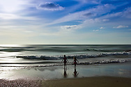 Conceptual beach scene with two small female children watching the waves