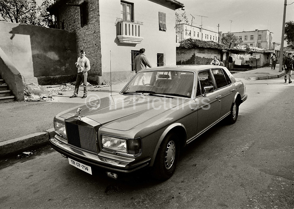 Rolls Royce on the streets of Tirana belonging to Hajdin Sejdija, a Kosovar from Switzerland, who began a series of investment projects through the Swiss-Albanian Illyrian Bank. The culmination was a proposals for a Sheraton hotel in central Tirana which collapsed after building just the foundations. The enormous hole which quickly filled with weeds & rubbish became known as Sejdija's hole. Unbeknown to the Albanian authorities, Sejdija was wanted for fraud in the UK and subsequently arrested in Switzerland.