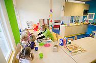 Nederland, Helmond, 20091111...Kinderdagverblijf de Bereboot is een nieuw kdv dat is gestart op een landgoed in een mooie ruime en groene omgeving. ..De gezamelijke broodmaaltijd. De kinderen zitten aan tafel met elk een bekertje drinken voor zich.....Netherlands, Helmond, 20091111. ..Childcare, The nursery the Bear boot is on an estate in a beautiful and spacious green surroundings.    ..