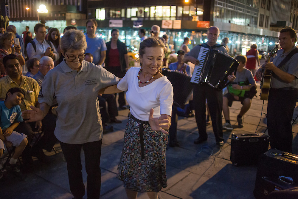 Two women dance to the music of The Old Aker Band (Gamle Aker Spelemannslag), a Norwegian accordion band, at Accordions Around the World in Bryant Park.
