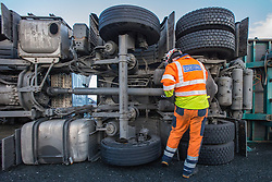 © Licensed to London News Pictures . 05/12/2013 . Manchester , UK . A man examines the underside of the overturned lorry . An overturned lorry on the Barton Bridge on the M60 orbital road around Manchester as very high winds causes damage across the UK . Photo credit : Joel Goodman/LNP