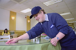 Woman with learning disability wiping tables in café,
