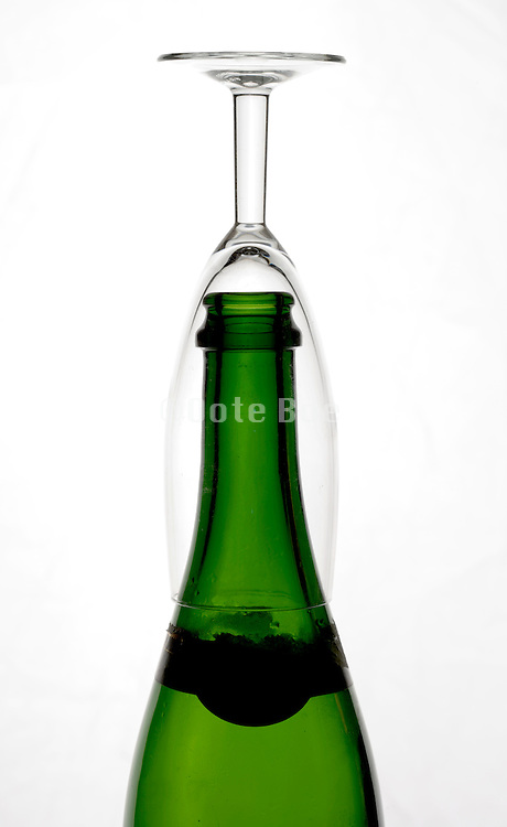 empty champagne bottle with glass placed upside down on top of it