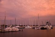 A hazy sunset illuminates Newport harbor and the American Shipyard with an unusually dramatic orange glow.