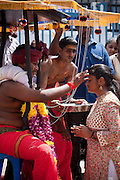 Offerign a blessing at Thaipusam Festival, Batu Caves, Malaysia. It is a Hindu festival celebrated mostly by the Tamil community on the full moon in the Tamil month of Thai (Jan/Feb). The festival celebrates the birth of Murugan,the youngest son of Shiva and his wife Parvati. The festival at Batu Caves, Kuala Lumpur culminates in a 272 step climb into the cave.