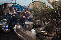 Wendover, UK. 10 January, 2020. Stop HS2 activists sit around a camp fire at the newly-established Wendover Active Resistance Camp. Activists from around the UK established the camp in woodland outside Wendover on the proposed route for HS2 through the Chilterns AONB in response to requests for assistance from members of the local community opposed to the high speed rail link. The impact on the immediate area is expected to be even worse than initially expected, with not only two 500m viaducts and a 1km embankment to be constructed but also a Bentonite factory and 240-bed accommodation block.