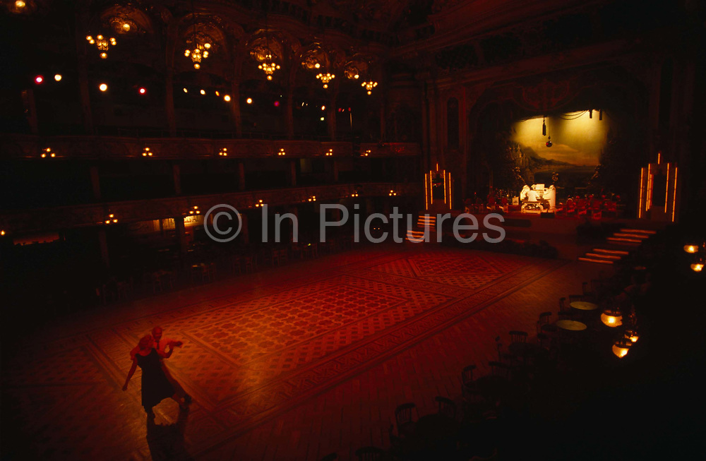 An elderly retired couple pause on the wide but darkly lit dance floor at Blackpool Tower Ballroom, England. They are the only dancers in the empty dance space, except for the Wurlitzer organist who is playing his accompanying music at the front of the stage, in a pool of bright light. We are looking down from a balcony high above and the husband and wife are pausing during their dance routine, stopping just long enough to register as sharp figures in the picture. The light is orange and red because of the tungsten light source. The Ballroom is the traditional home of the mighty Wurlitzer Organ and complemented by the 3 Deck Wersi - the world's most advanced organ. The Wersi is a state-of-the-art Louvre organ which is played by the resident organists in this magnificent setting. The present interior of the Blackpool Tower circus  was created by the famous theatre designer, Frank Matcham and completed in 1900.