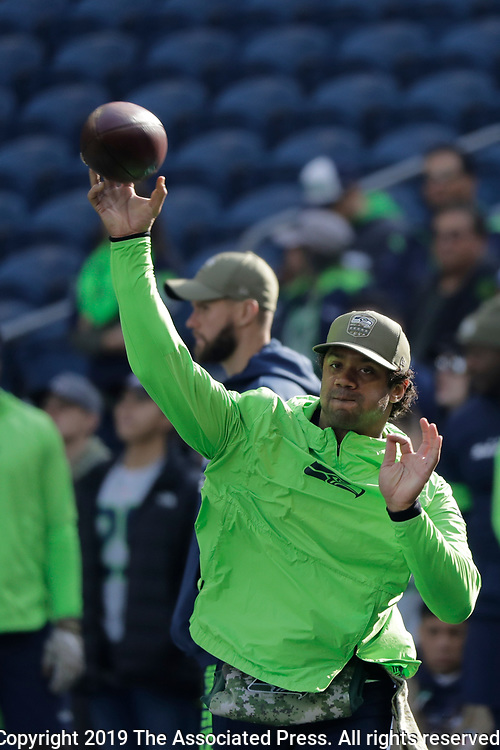 Seattle Seahawks quarterback Russell Wilson wears a hat showing the Seahawks NFL football Salute to Service logo as he warms up before an NFL football game against the Tampa Bay Buccaneers, Sunday, Nov. 3, 2019, in Seattle. (AP Photo/John Froschauer)