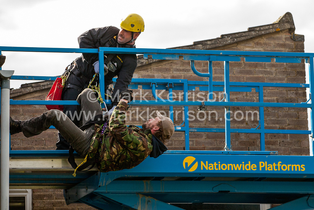 A housing activist hangs off a cherry picker being used by bailiffs for evictions from the Sweets Way housing estate on 23rd September 2015 in London, United Kingdom. A group of housing activists calling for better social housing provision in London had occupied some of the properties on the 142-home estate in Whetstone, in some cases refurbishing properties intentionally destroyed by the legal owners following eviction of the original residents, in order to try to prevent the eviction of the last resident on the estate and the planned demolition and redevelopment of the entire estate by Barnet Council and Annington Property Ltd.