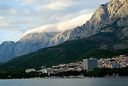 View from the sea of the northern part of Makarska, with clouds spilling over the Biokovo National Park, part of the Dinaric Alps, in the background. Makarska, Croatia