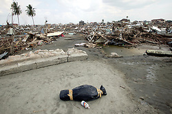 A small body lies wrapped in a black body bag close to a semi destroyed house. Children were helpless to escape the ferocity of the waves. Areas of Banda Aceh that were closer to the sea saw almost total destruction, where most buildings were more simply constructed of cheaper materials.  Brick built in parts, but without concrete supports. The wood flotsam was coming from thousands of homes of poorer groups in society that had colonized marginal land close to the beach, these were all completely destroyed, and their occupants, of whom little was probably known, washed back out to sea or trapped under debris further inland.