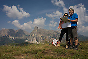 Hiking couple consult their map with panoramic views of mountain tops behind in the Pralongià above San Cassiano-St. Kassian in the Dolomites, south Tyrol, northern Italy. In winter, the Pralongià meadows are the heart of Alta Badia's skiing area. Hiking trails lead across the high alpine pastureland between Corvara and San Cassiano (St. Kassian) with hilly upland meadows with vast mountain pastures and many old hay huts, a pretty group of trees at the edges of the meadows, and the beautiful shapes of the surrounding mountains, which include the Gruppo di Sella (Sellastock) Massif, Sassongher, Monte Cavallo (Heiligkreuzkofel), Cunturines and Lagazuoi.