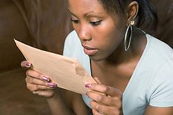 Teenage girl looking at exam result envelope,