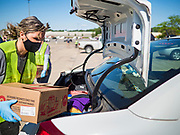 29 MAY 2020 - DES MOINES, IOWA: LILIA DOMNENKO, a volunteer, loads a box of produce in a car during a produce distribution in a mall parking lot in Des Moines. The Des Moines Area Religious Council (DMARC) and Capitol City Fruit from Norwalk, IA, gave away 1,800 boxes of fresh produce with a mix of vegetables and fruit. The boxes contain enough produce to feed a family of four for a week. The produce was provided by the USDA Farmers to a Families food program. Because of the COVID-19 pandemic, the unemployment rate in Iowa hit 10.2% in May, the highest unemployment rate ever recorded in Iowa and food insecurity in Iowa is impacting communities throughout the state.         PHOTO BY JACK KURTZ