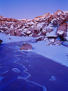 Ice-covered wash and Sonsela Sandstone boulders dusted with snow at dusk, Blue Mesa, Petrified Forest National Park, Arizona.