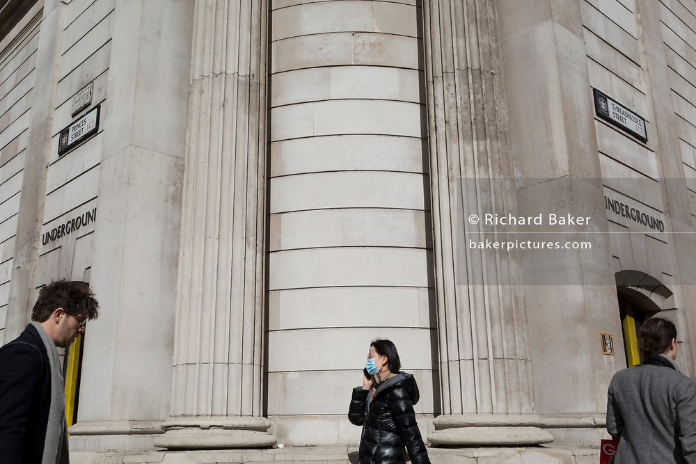 On the day that Chancellor of the Exchequer Rishi Sunak unveiled a £30bn package to boost the economy and get the country through the coronavirus outbreak, an Asian lady wearing a surgical mask walks past Bank Underground Station in the capital's financial district, as the Bank of England's governor Mark Carney cut the interest rate from 0.75% to 0.25%, on 11th March 2020, in the City of London, England.