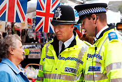 Policeman and Community Support Officer chat to an elderly woman in local market; Knaresborough; Scarborough; Yorkshire UK