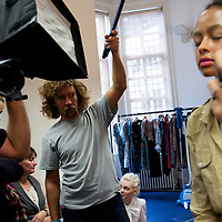A photographer, and his assistant holding a secondary flash, document a model being styled backstage before showing the Saloni autumn/spring 2010/2011 collection during a fashion show held in the map room of the Royal Geographical Society, South Kensington, London on 20 September 2010.