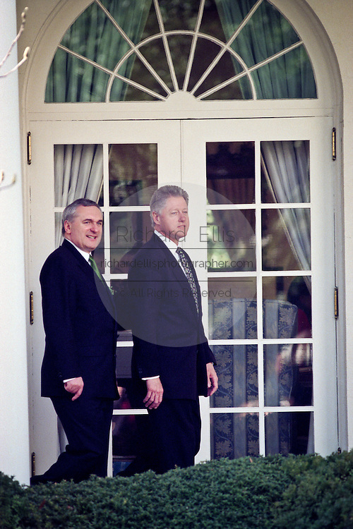 President Bill Clinton comments on the spring like weather as he walks through the Rose Garden with Irish Prime Minister Bertie Ahern March 17, 1999 before a a St. Patrick's Day event.