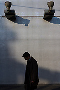 A Japanese male office worker, known as a salaryman walks past a wall in Shinjuku, Tokyo, Japan. Thursday February 15th 2018