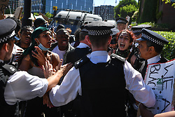 © Licensed to London News Pictures. 31/05/2020. London, UK. Protesters react as a woman is arrested and led off by police. Demonstrators gathered in front of the US Embassy in London, protesting the police killing of George Floyd, an unarmed black man in Minneapolis who died in police custody while an officer kneeled on his neck to pin him down. Photo credit: Guilhem Baker/LNP