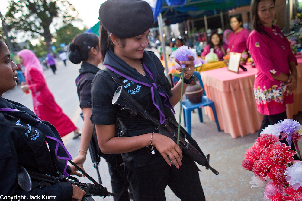 Sept. 29, 2009 -- YARANG, THAILAND: A member of the women's Ranger unit shops for paper flowers during a security operation at the night market in Yarang, Thailand. The 39 women in the 44th Army Ranger Regiment are the only Thai women seeing front line active duty against Moslem insurgents in Thailand's deep south provinces of Pattani, Narathiwat and Yala. All of the other women serving in Thai security services are employed as office and clerical workers. The Ranger women are based at the Ranger camp in the Buddhist village of Baan Trokbon in Sai Buri district of Pattani province. The unit was formed in 2006 after Muslims complained about the way Thai soldiers, all men, treated Muslim women at roadblocks and during security sweeps. The women are frequently called upon to back up Thai regular army units when they are expected to encounter a large number of Muslim women. At least two of the women have been killed by Muslim insurgents. The unit has both Muslim and Buddhist members. Many of the women in the unit joined after either their fathers or husbands were killed by insurgents.  Photo by Jack Kurtz / ZUMA Press