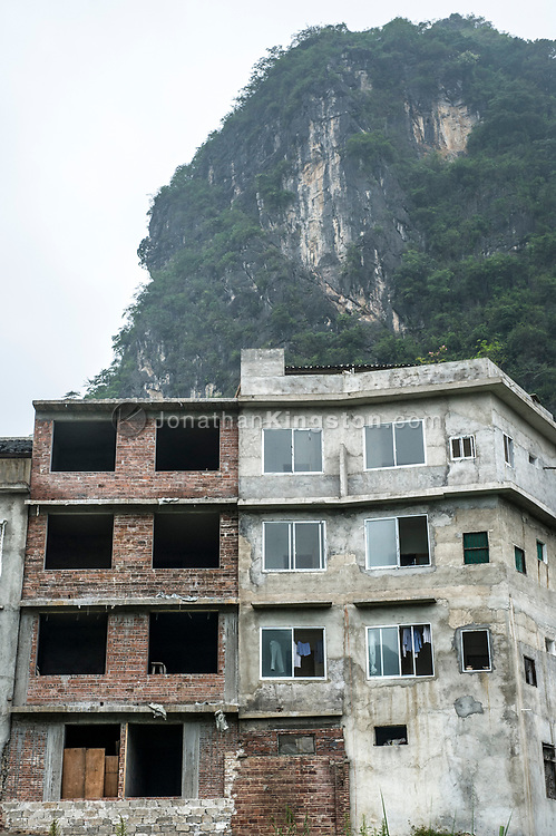 Low angle view of an unfinished brick and concrete apartment building in Yangshuo, China.