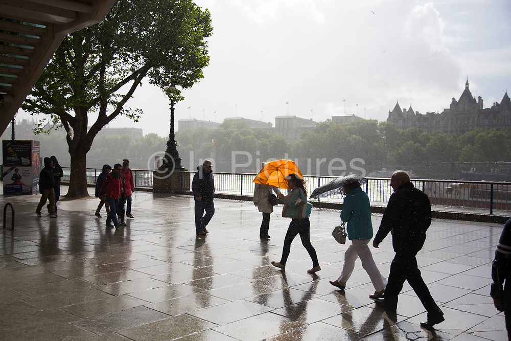People walk fast to find cover from a sudden rain shower on the riverside walkway. The South Bank is a significant arts and entertainment district, and home to an endless list of activities for Londoners, visitors and tourists alike.