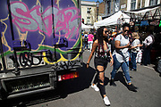 Friends walk along Portobello Road Market past a graffiti covered van in Notting Hill, West London, England, United Kingdom. People enjoying a sunny day out hanging out at the famous Sunday market, when the antique stalls line the street.  Portobello Market is the worlds largest antiques market with over 1,000 dealers selling every kind of antique and collectible. Visitors flock from all over the world to walk along one of Londons best loved streets.