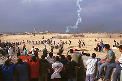 Palestinians run for cover from Israeli soldiers Friday , October 20, 2000 in Gaza. The agreement reached at the crisis summit in Egypt which was meant to stop the spiral of violence in the Middle East is unravelling rapidly throughout Gaza and the West Bank.(Photo by Ami Vitale)