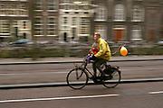 Een man fietst met een kind voorop door Amsterdam.<br /> <br /> A man is cycling with a child at the front of the bike in Amsterdam.