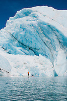 One adult on a stand up paddle board (SUP) paddles past an iceberg on Bear Lake in Kenai Fjords National Park, Alaska.