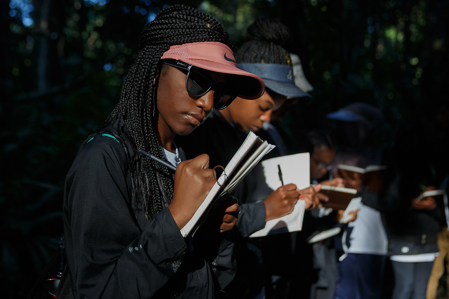 Kendall Hall, 15, joins other kids in taking notes in their journal while hiking in the jungle. The kids are required to take notes in their journal everyday while on the trip.