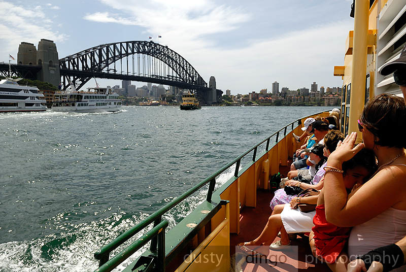 Passengers aboard Sydney Harbour ferry, with Sydney Harbour Bridge in background. Circular Quay, Sydney, Australia