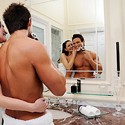 A healthy looking man shaving in a hotel room whilst enjoying the company of an attractive female companion.