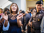 """14 FEBRUARY 2015 - BANGKOK, THAILAND: NATCHACAH KONG-UDOM, left, a Thai democracy advocate, leads a chant in front of a police officer during a protest against the military coup. Dozens of people gathered in front of the Bangkok Art and Culture Centre in Bangkok Saturday to hand out red roses and copies of George Orwell's """"1984."""" Protestors said they didn't support either Red Shirts or Yellow Shirts but wanted a return of democracy in Thailand. The protest was the largest protest since June 2014, against the military government of General Prayuth Chan-Ocha, who staged the coup against the elected government. Police made several arrests Saturday afternoon but the protest was not violent.    PHOTO BY JACK KURTZ"""