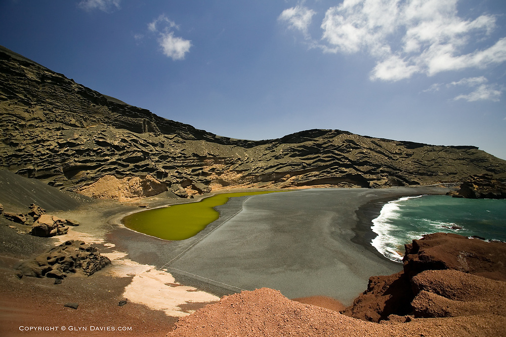 The Atlantic ocean waves push up the black lava shingle towards the volcanic crater lake in an exploded caldera, El Golfo, West Lanzarote coast. The lake is coloured green by Olivine.