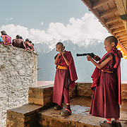 Young monks playing with fake plastic guns. The Tshechu of the Gasa monastery on the road leading to Laya. Tshechu are annual religious Bhutanese festivals held in each district on the tenth day of a month of the lunar Tibetan calendar. Tshechus are large social gatherings, which perform the function of social bonding among people of remote and spread-out villages.