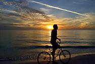 USA: Florida: Sarasota County: Sarasota: Silhouette of a bicyclist against a beautiful sunset on Lido Beach.